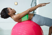 African woman doing series of sit-ups in gym — Stock Photo