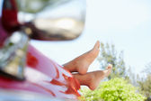 Woman lying in cabriolet car with feet out of window — Stock Photo