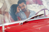 Girlfriend and boyfriend flirting in red old car — Stock Photo