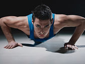 Man doing push-ups on black background — Stock Photo