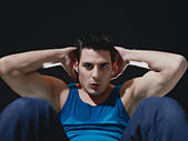 Man doing series of sit-ups on black background — Stock Photo