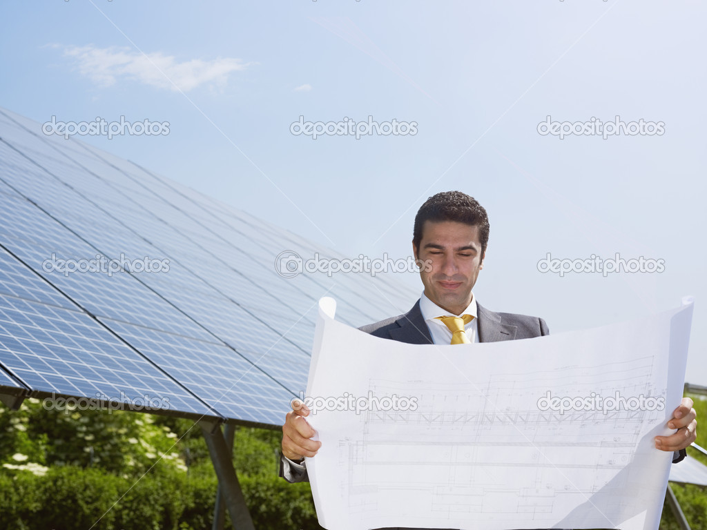 Portrait of mid adult italian male engineer reading blueprints in solar power station and smiling. Horizontal shape, front view. Copy space — Stock Photo #9301240