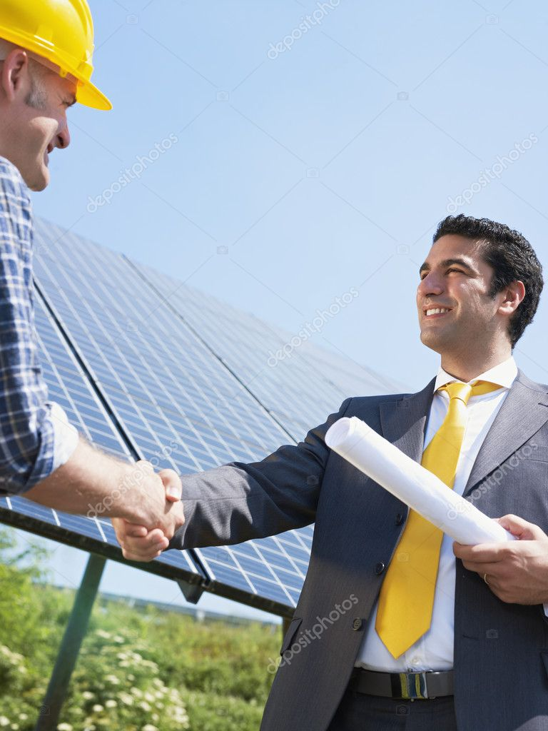 Portrait of mid adult italian male engineer holding blueprints and shaking hands to manual worker in solar power station. Vertical shape, low angle view. Copy space — Stock Photo #9301258