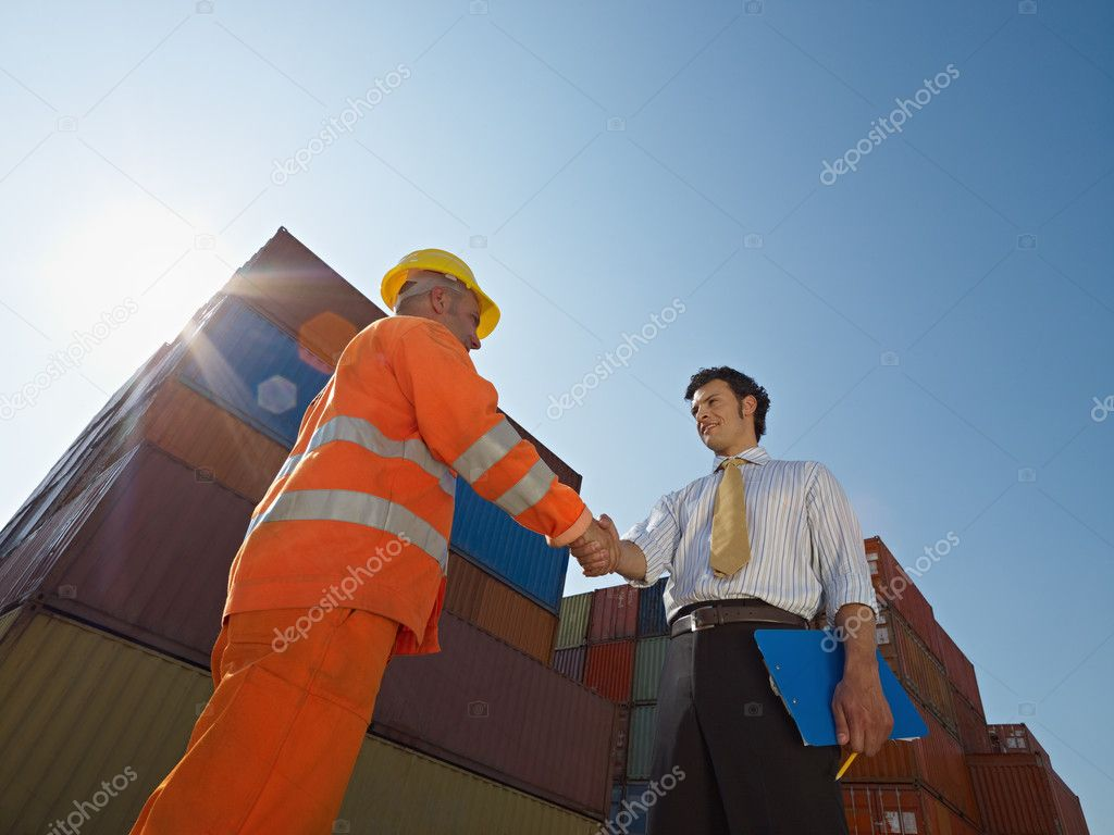 Mid adult businessman holding clipboard and shaking hands to manual worker near cargo containers. Horizontal shape, low angle view. Copy space — Stock Photo #9302074