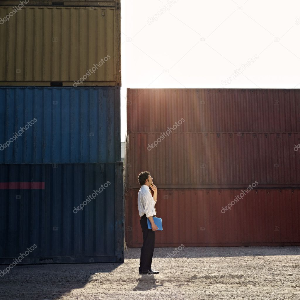 Mid adult businessman standing near cargo container with hand on chin and looking up. Square shape, full length, side view, copy space — Stock Photo #9302076