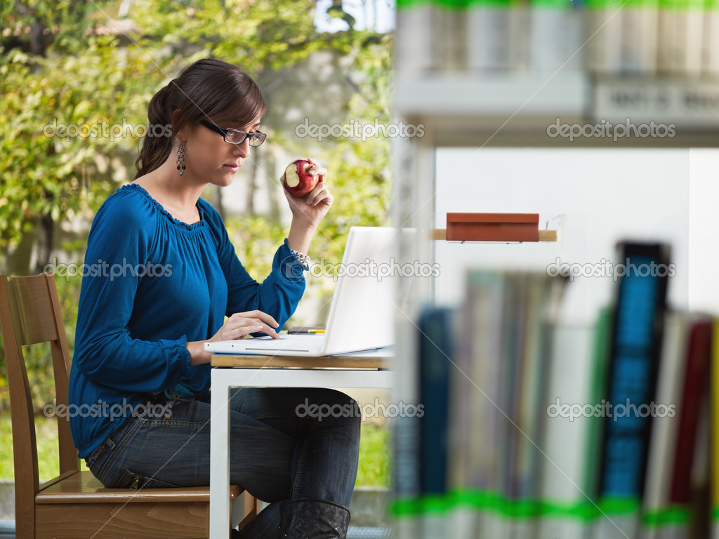 Female college student studying in library and eating red apple. Horizontal shape, side view, three quarter length — Stock Photo #9303335