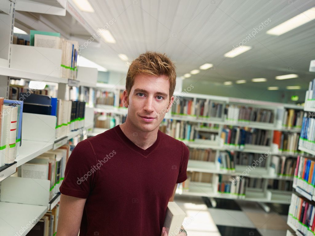 Male college student with book standing near shelf in library. Horizontal shape, front view, waist up, copy space  Stock Photo #9303365