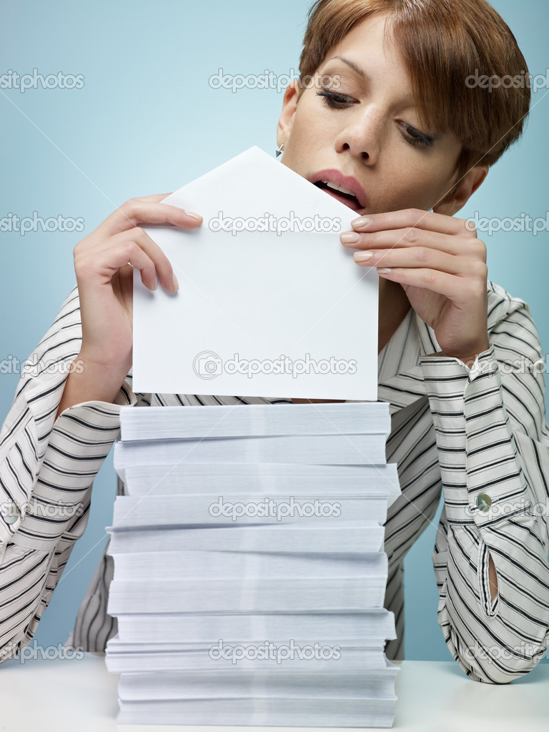Caucasian secretary closing pile of envelopes. Vertical shape, front view, waist up, copy space  Stock Photo #9304180