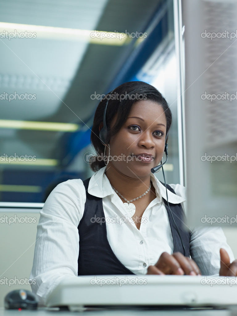Female african american customer service representative talking on the phone and typing on pc. Vertical shape, front view — Stock Photo #9304309