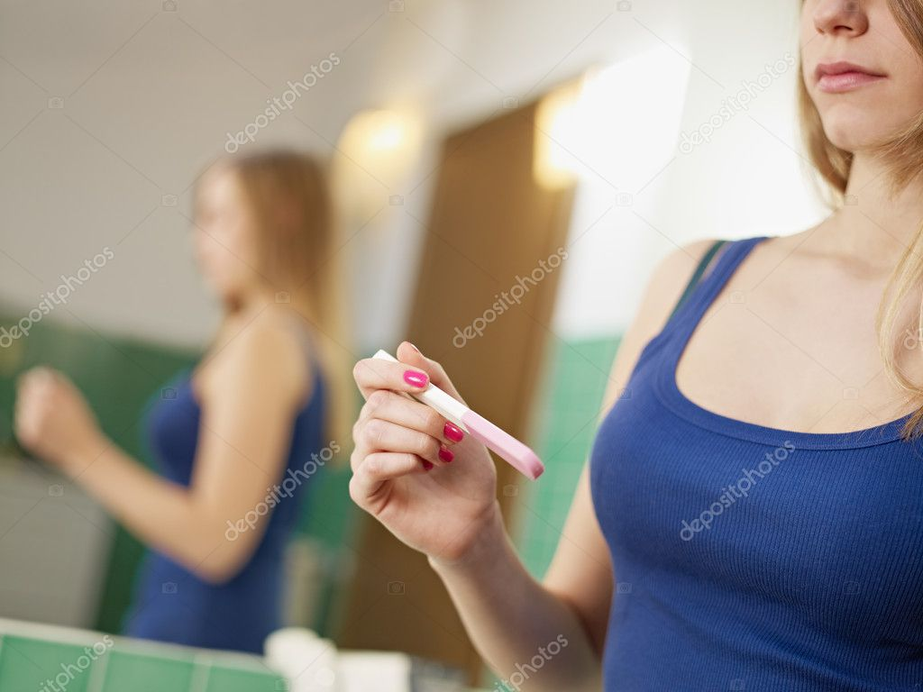 Young caucasian woman in tanktop holding pregnancy test, waiting for results. Horizontal shape, cropped view — Stock fotografie #9304452