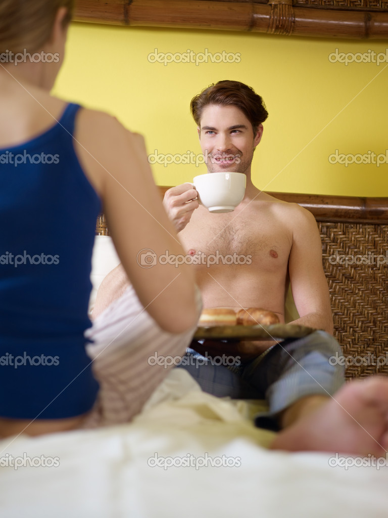 Caucasian heterosexual couple eating croissant and drinking coffee in bed. Vertical shape, rear view, focus on background — Stock Photo #9304454