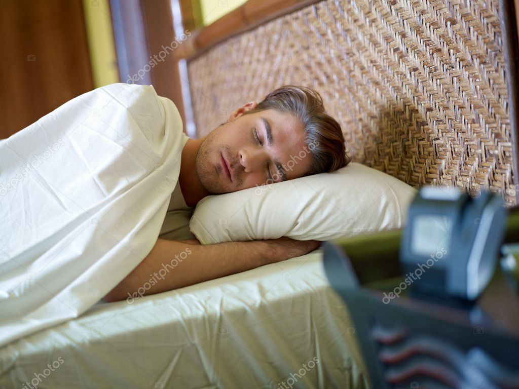Serene caucasian adult man lying in bed with alarm clock in foreground. Horizontal shape, waist up, front view — Stock Photo #9304460