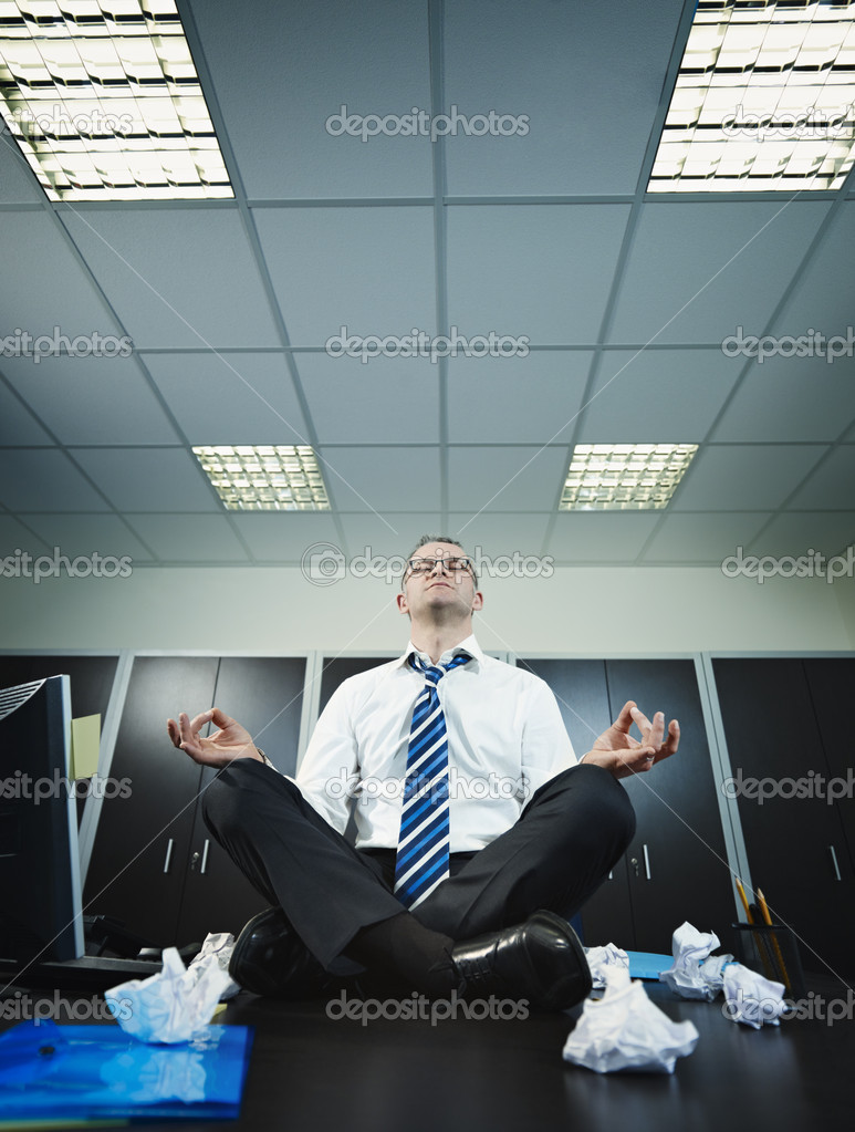 Stressed businessman sitting on desk in lotus position. Vertical shape, full length, Copy space  Stock Photo #9304663