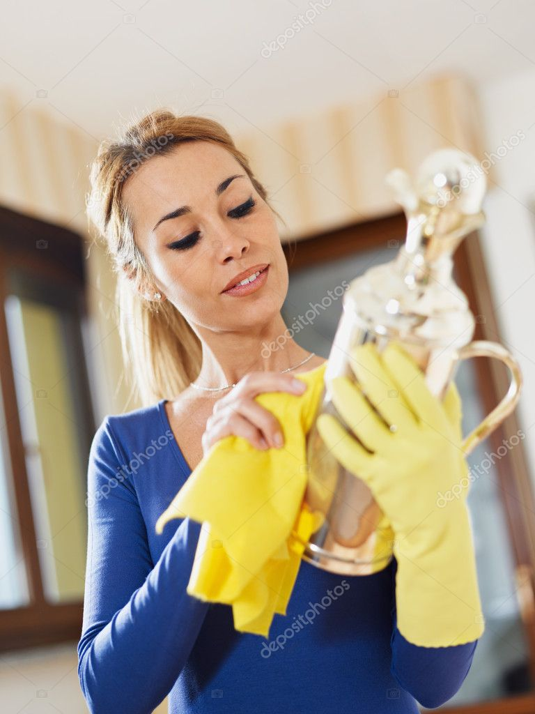 Portrait of woman with yellow gloves rubbing silver object. Vertical format — Stock Photo #9304985