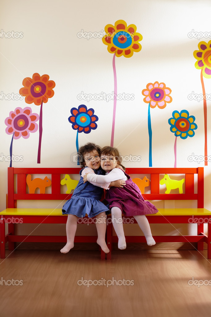 Caucasian and hispanic female preschoolers sitting on bench in kindergarten, playing and smiling. Vertical shape, full length, front view — Stock Photo #9305093