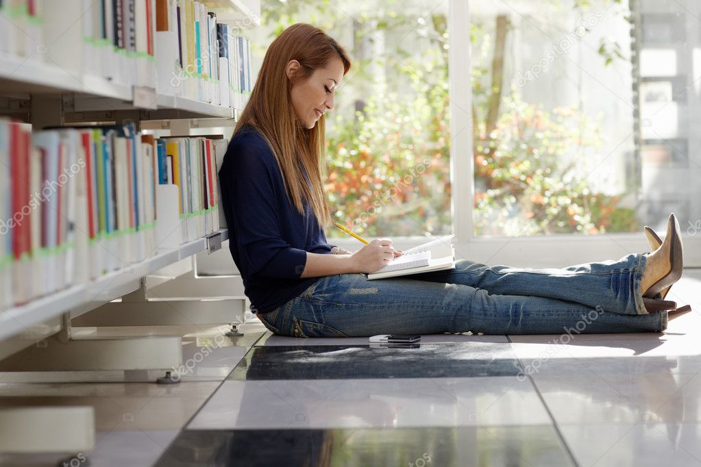 Female college student sitting on floor in library, reading book and taking notes. Horizontal shape, side view, full length, copy space — Stock Photo #9305168
