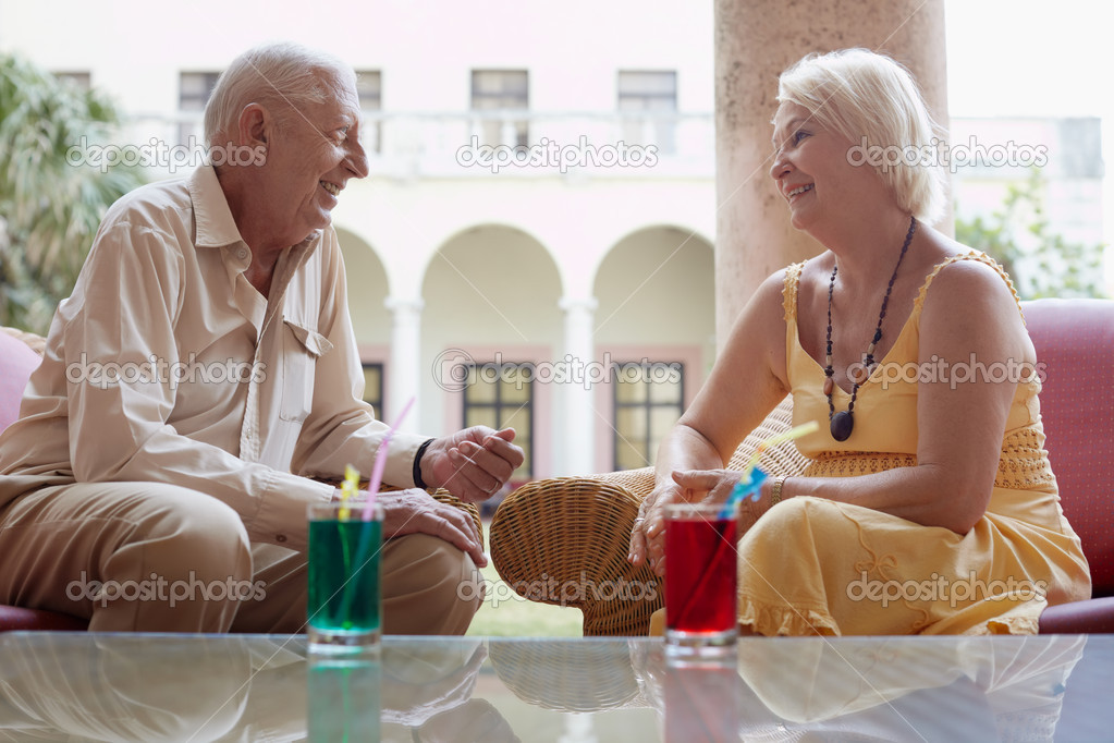 Senior caucasian couple sitting in bar at hotel with cocktails and talking. Horizontal shape, side view — Stock Photo #9305291