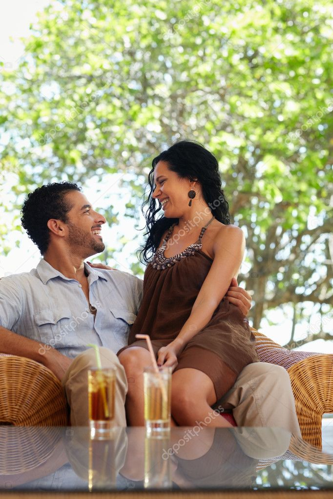 Honeymoon: young just married hispanic couple sitting on armchair in hotel bar. Vertical shape, copy space — Stock Photo #9305526