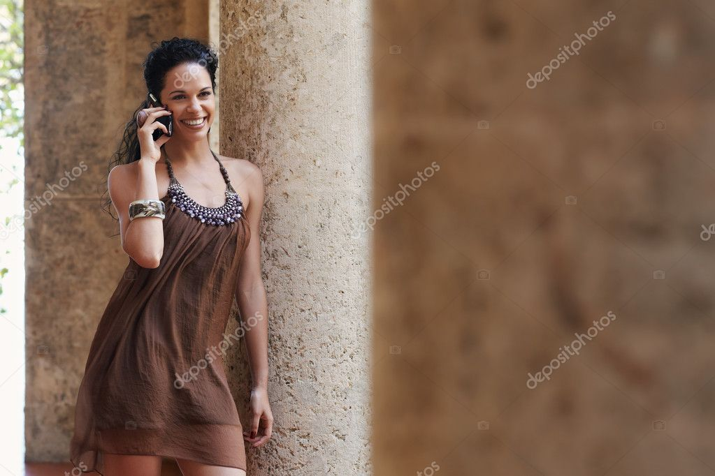 Mid adult hispanic woman talking on mobile phone and leaning on columns outdoors. Horizontal shape, front view, copy space  Stock Photo #9305528