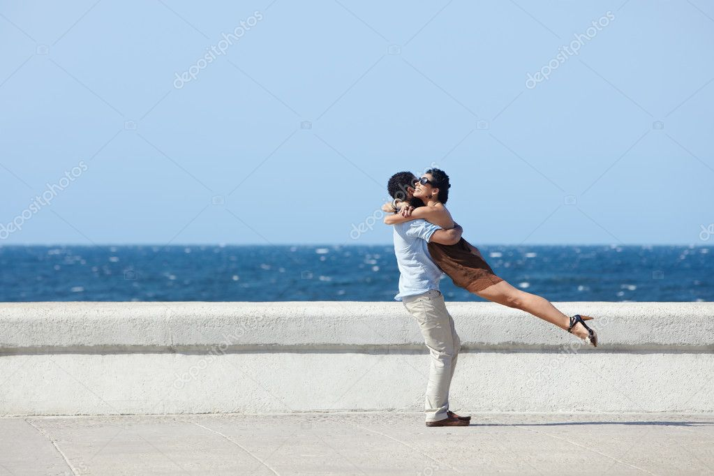 Euphoric young couple meeting and hugging near the sea. Horizontal shape, side view, copy space  Stock Photo #9305538