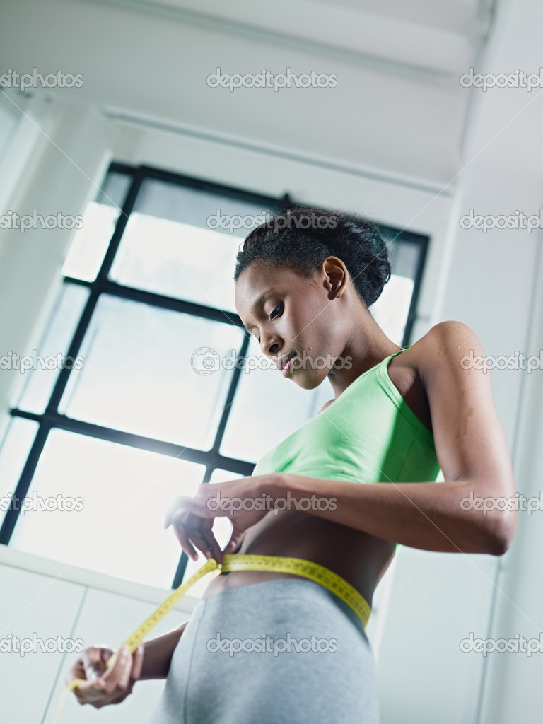 Young african american woman in green sportswear holding tape on belly and measuring weight loss. Vertical shape, side view — Stock Photo #9305656