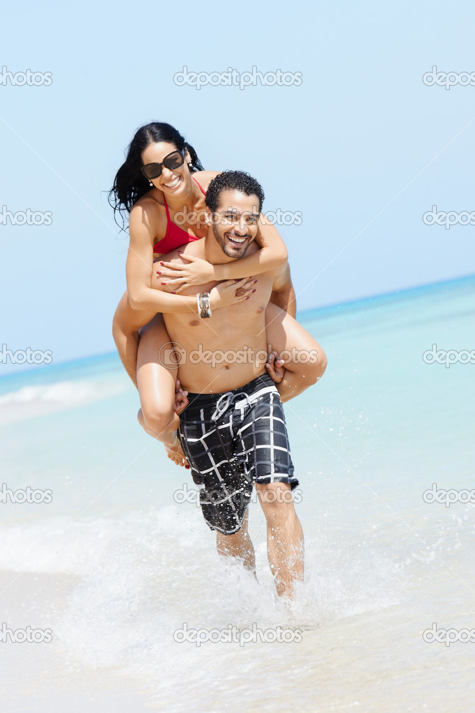 Happy maried adult couple having fun and playing on the sea shore in cuba. Vertical shape, full length, copy space — Stock Photo #9306279