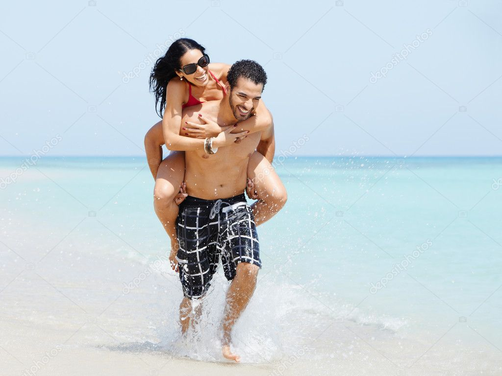 Happy maried adult couple having fun and playing on the sea shore in cuba. Horizontal shape, full length, copy space — Stock Photo #9306281