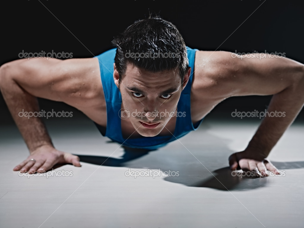 Young caucasian male in sportswear doing push ups on black background. Horizontal shape, front view, copy space — Stock Photo #9306613