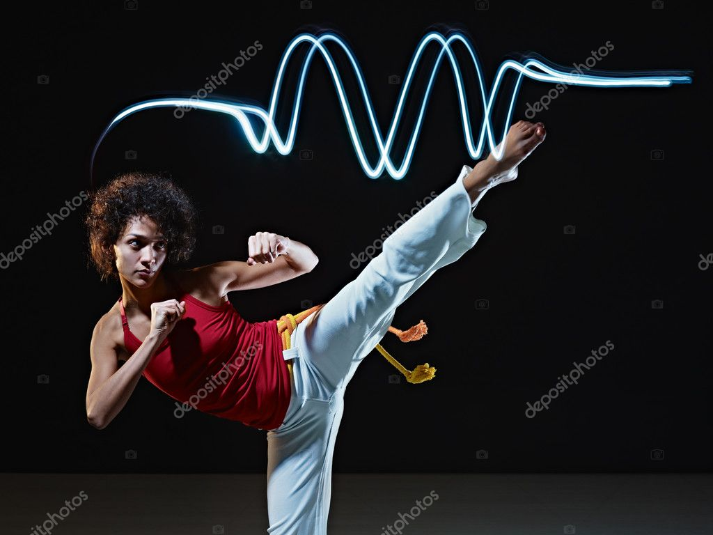 Young adult latin american female doing capoeira side kick in gym, with streaks of led lights on top. Vertical shape, full length, front view, copy space  Stock Photo #9306657