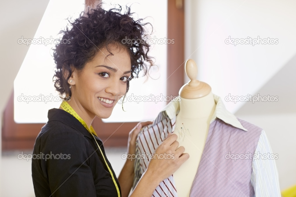 Young hispanic female dressmaker adjusting clothes on tailoring mannequin and smiling at camera. Horizontal shape, side view, waist up — Stock Photo #9306690