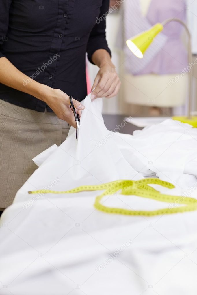 Young hispanic female dressmaker cutting white fabric for bridal gown. Vertical shape, front view, selective focus, copy space  Stock Photo #9306701