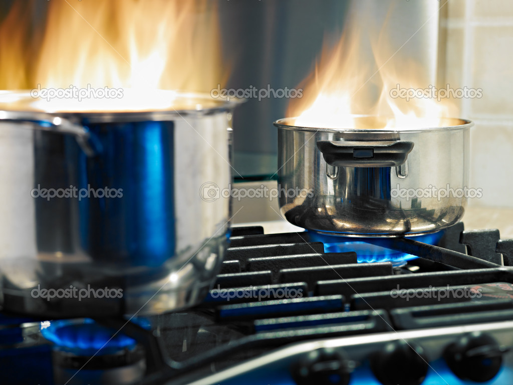 Pans in fire on stoves. Horizontal shape — Stock Photo #9306863