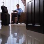 Geschäftsmann mit digitalen TabletPC in Hotelzimmer — Stockfoto