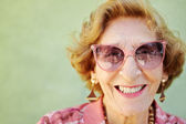 Aged woman with pink eyeglasses smiling at camera — Stock Photo