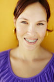 Young woman with orthodontic braces smiling — Stock Photo