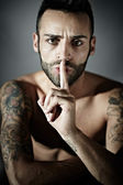 Tattooed man with finger on mouth — Stock Photo
