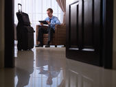 Businessman using digital tablet pc in hotel room — Stock Photo