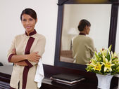 Asian maid working in hotel room and smiling — Stock Photo