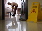 Maid at work and cleaning in luxury hotel room — Stok fotoğraf