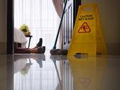 Femme de ménage glissé sur le sol humide et pose — Photo