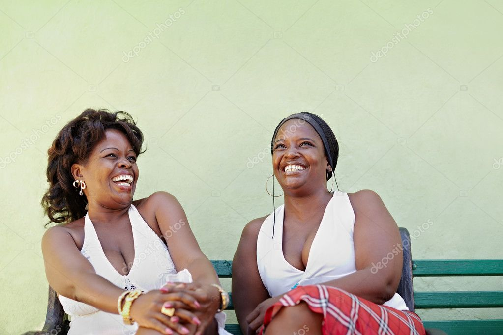 Portrait of two happy african adult women talking on bench and smiling. Horizontal shape, copy space — Stock Photo #9748239