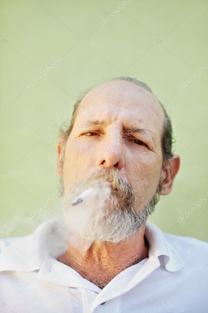 Portrait of mature white man looking at camera against green wall with cigarette in mouth. Copy space  Stock Photo #9748467