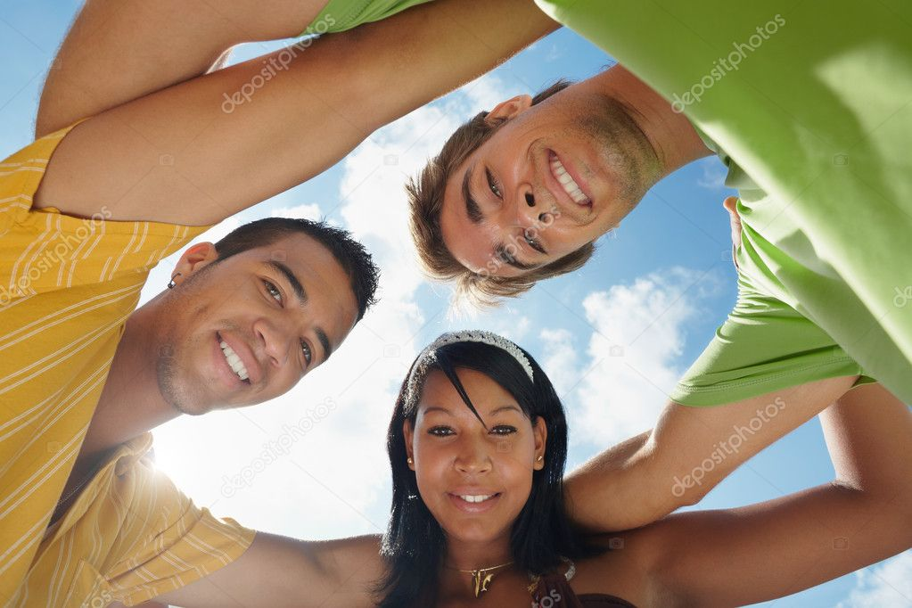 Multiethnic group of male and female friends hugging and looking at camera with sky in background. Low angle view  Stock Photo #9748689