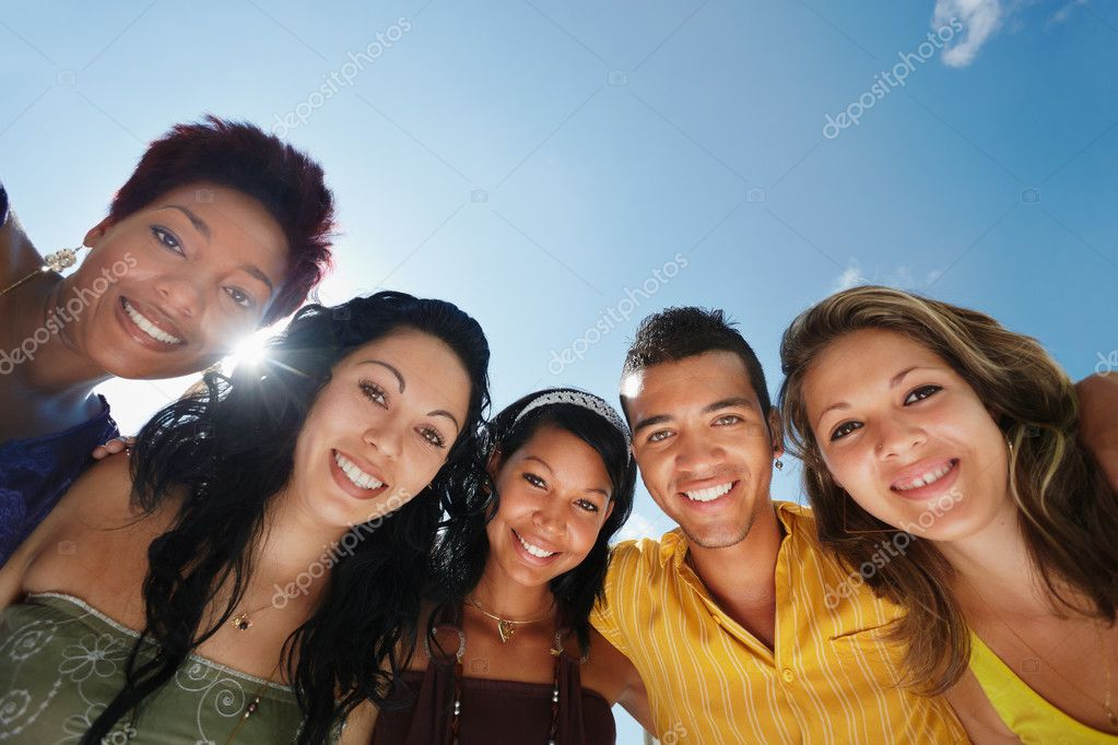 Multiethnic group of five male and female friends hugging and looking at camera with sky in background. Low angle view, copy space — Stock Photo #9748733