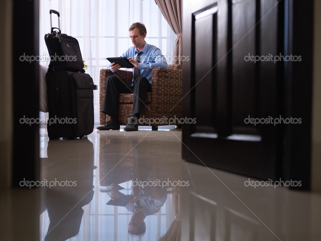 Mid adult caucasian manager typing on tablet pc in hotel room during business travel. Low angle view, full length — Photo #9749284