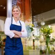 Young pretty woman working as florist in shop and smiling - Stock Photo