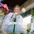 Blonde girl working in flowers shop with roses and gerbera — Stockfoto