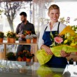 Young woman and client in flowers shop - Stock Photo