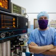 Portrait of surgeon looking at camera in clinic operation room - Stock Photo
