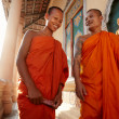 Two monks meet and salute in a buddhist monastery, Asia - Stock Photo